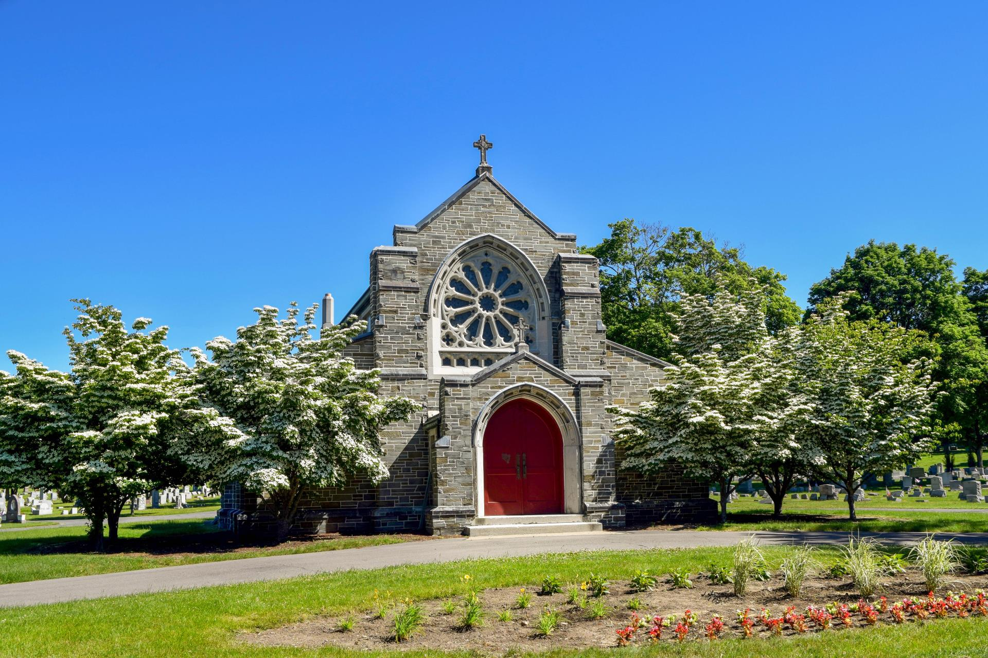 Stone chapel with red door surrounded by flower trees