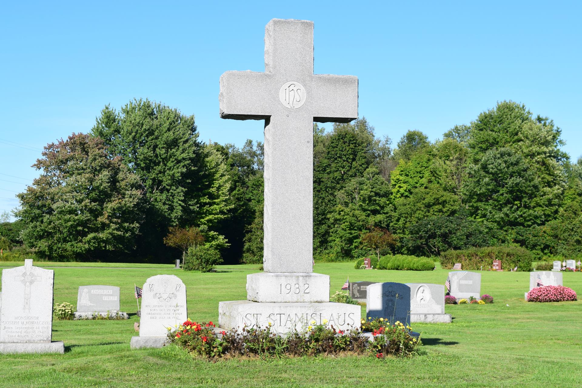 Burial area depicting a large cross monument and other small headstones